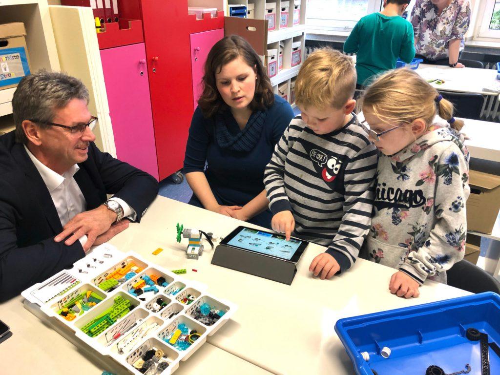 Ralph Hackelbörger, Ausbildungsleiter bei der Gea, (v.l.) lässt sich von Nina Wiesrecker, Leon und Estelle erklären, wie die Software funktioniert